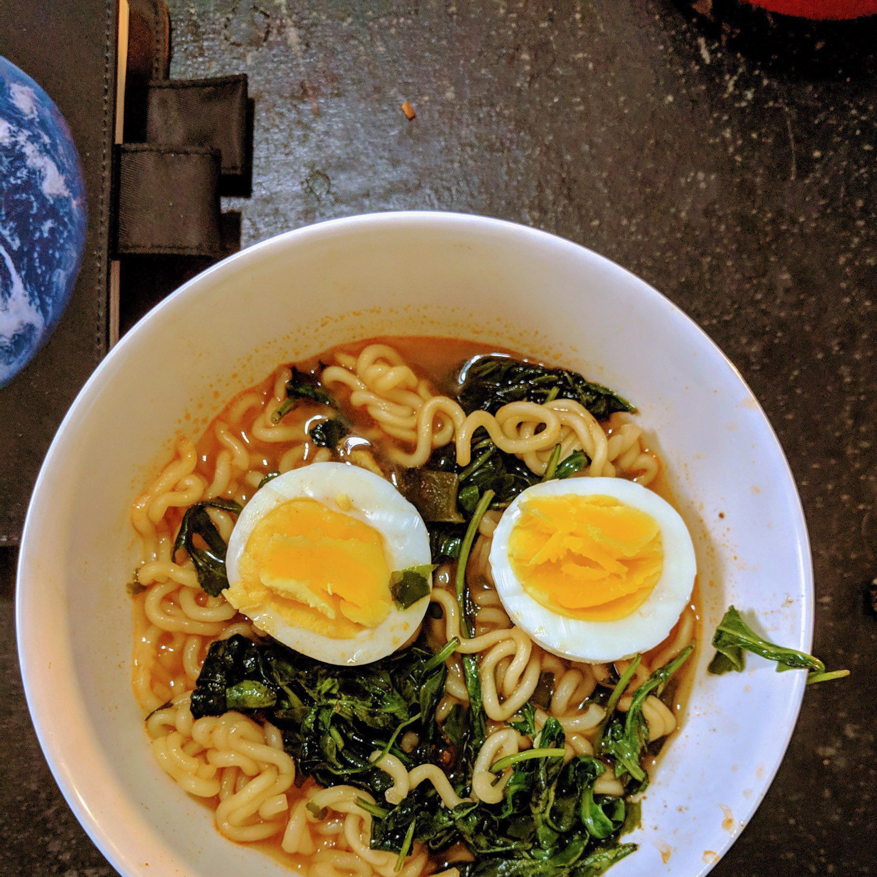 Ramen noodles in spicy broth with arugula and face up hardboiled egg